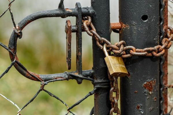 Czarna brama zamknięta łańcuchem z kłódką