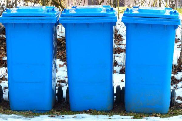 Trzy niebieskie kosze na śmieci w zimowej scenerii