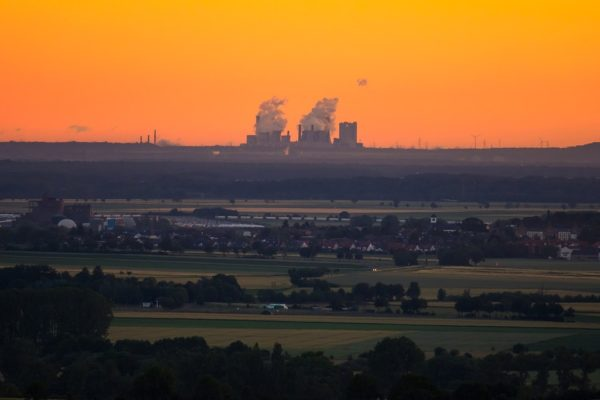 Panorama pól z dymiącą fabryką na horyzoncie o zachodzie słońca