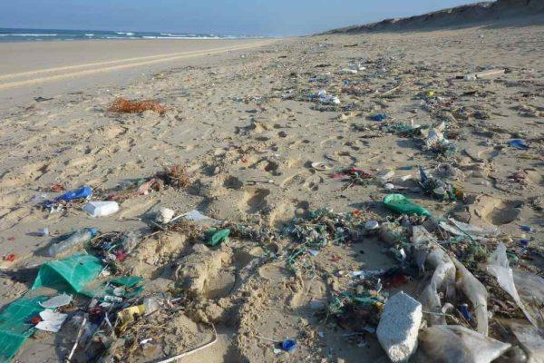 Odpady z tworzyw sztucznych zalegające na piaszczystej plaży