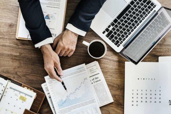 Przedsiębiorca z laptopem, raportami i kalendarzem na biurku, myślący jak nadążyć za zmianami prawa