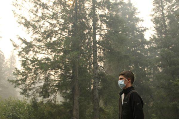 Mężczyzna w maseczce chroniącej przed smogiem na tle lasu