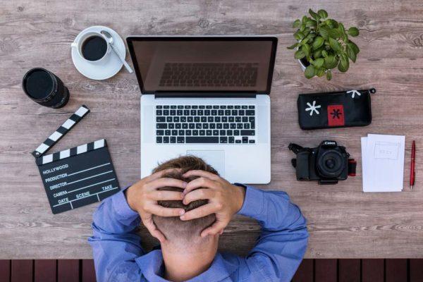 Przedsiębiorca siedzący przed laptopem zastanawiający się czy powinien się zarejestrować w BDO