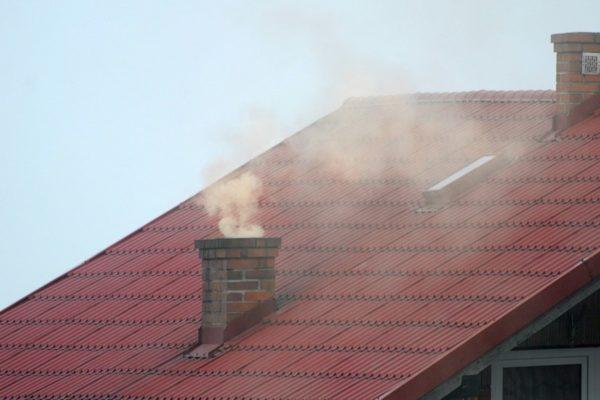 Dach z kominem, z którego wydobywa się dym ze starego rodzaju kotła, powodujący smog